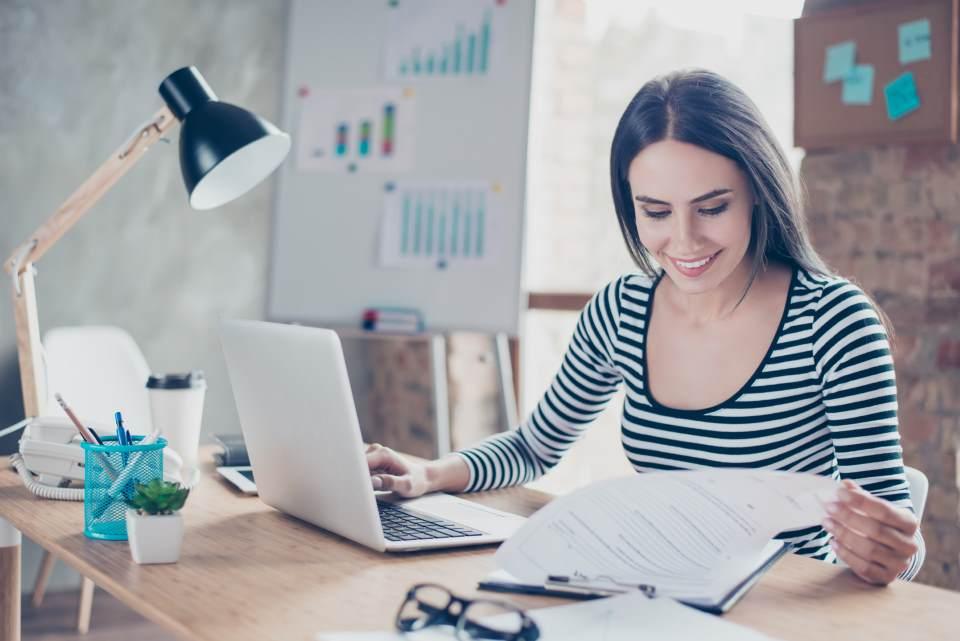 Frau am Schreibtisch sichtet Unterlagen