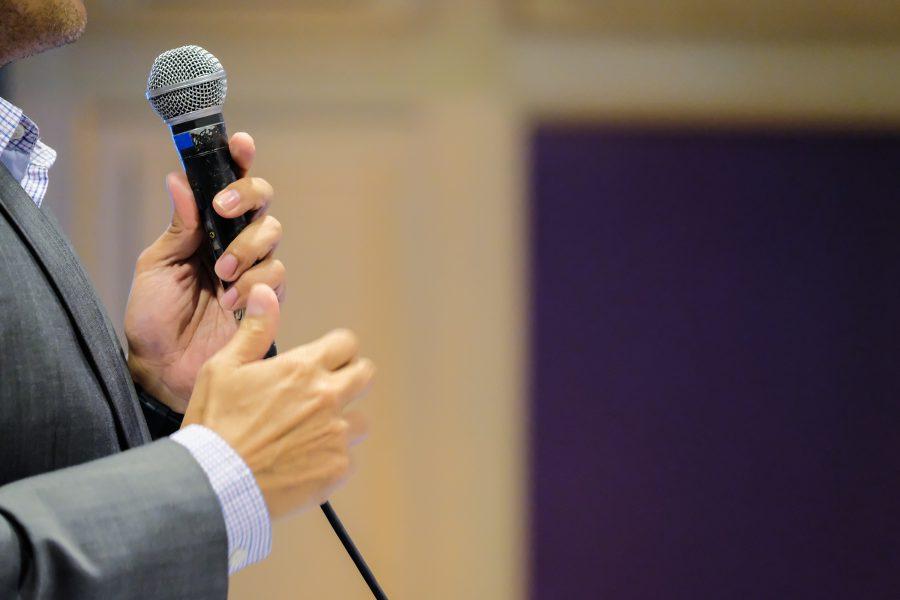 Redner mit Mikro vor Publikum