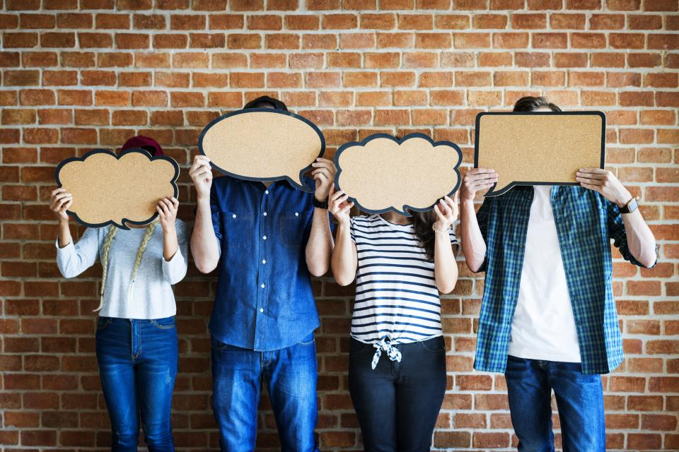 Junge Leute halten Sprechblasen vor Gesichter
