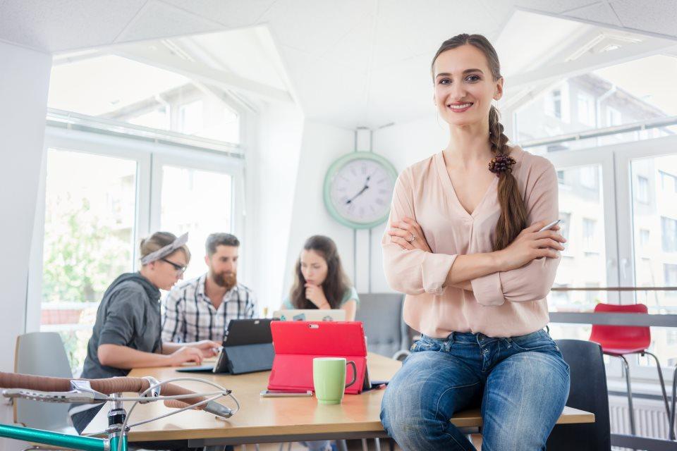 Startup Gründerin vor Kollegen am Schreibtisch