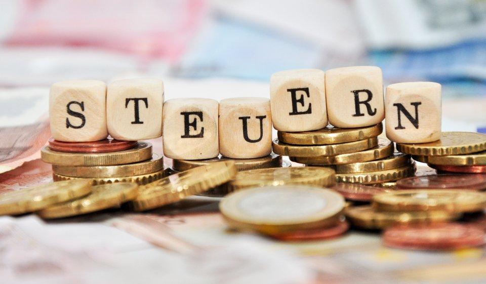 Würfel mit Aufschrift Steuern auf Geldmünzen