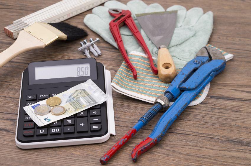 Werkzeug auf Tisch mit Geld und Taschenrechner