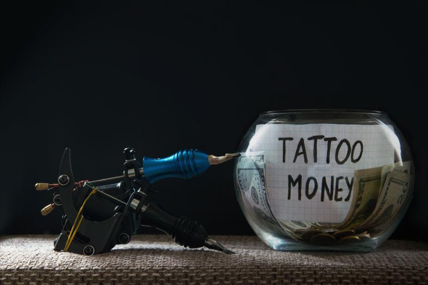 Tattoonadel neben Glas mit Geld