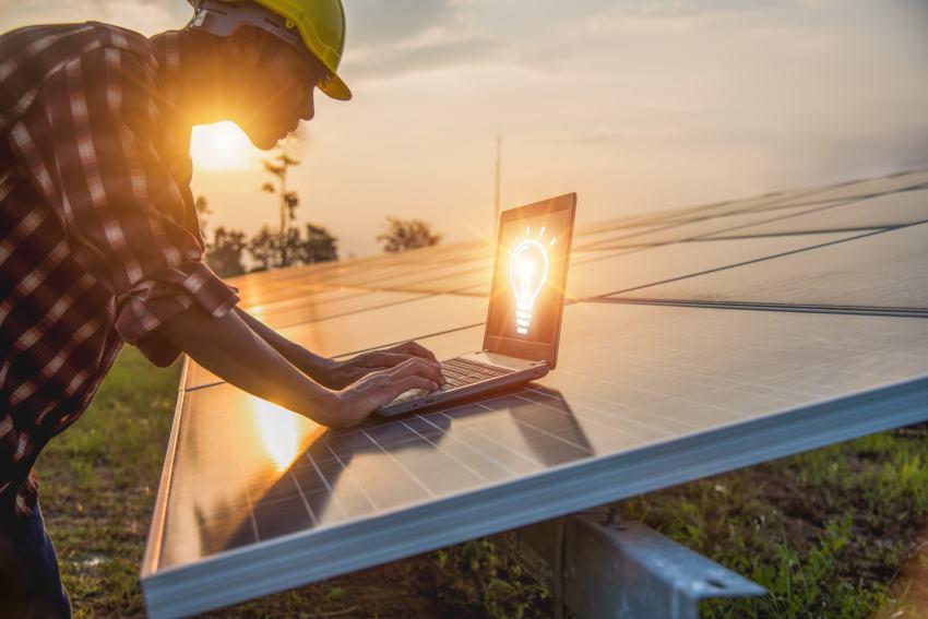 Umweltingenieur mit Laptop vor Solarfeld